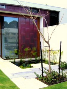 A copper and glass wall with a water feature and paving in front