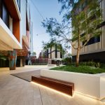 LIV Apartments lit up seating under tree